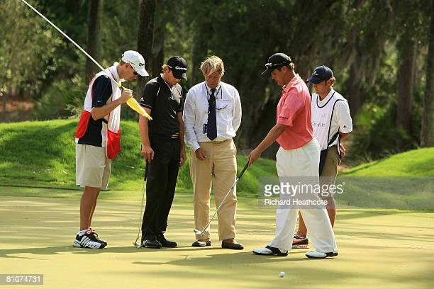 Sergio Garcia of Spain and Jeff Quinney talk with a rules official joined by their caddies on the 10th green during the final round of THE PLAYERS...