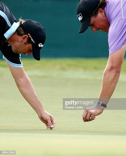 Sergio Garcia of Spain and Phil Mickelson repair divots on the 18th green during the final round of THE TOUR Championship presented by CocaCola at...