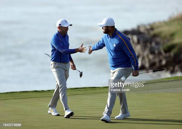 Sergio Garcia of Spain and team Europe and Jon Rahm of Spain and team Europe celebrate on the eighth green after winning the hole during Friday...