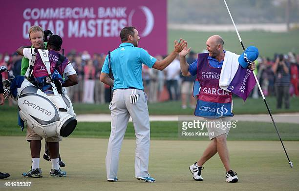 Sergio Garcia of Spain celebrates with his caddie after winning on the third playoff hole during the final round of the Comercial Bank Qatar Masters...