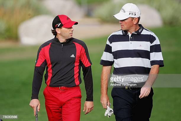 Sergio Garcia of Spain chats with Thomas Bjorn of Denmark on the 12th hole during the first round of The Abu Dhabi Golf Championship at Abu Dhabi...