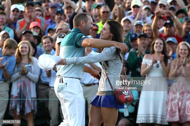 Sergio Garcia of Spain embraces fiancee Angela Akins in celebration after defeating Justin Rose of England on the first playoff hole during the final...