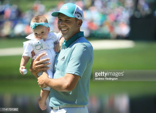 Sergio Garcia of Spain holds daughter Azalea Adele Garcia during the Par 3 Contest prior to the Masters at Augusta National Golf Club on April 10,...