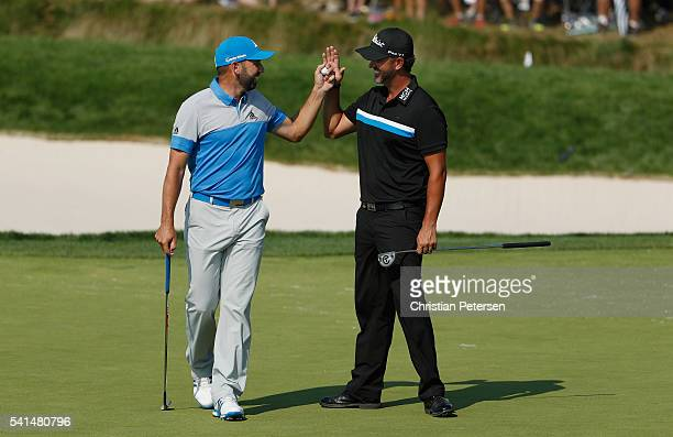 Sergio Garcia of Spain is greeted by Scott Piercy of the United States after Garcia holed a bunker shot for birdie on the eighth hole during the...