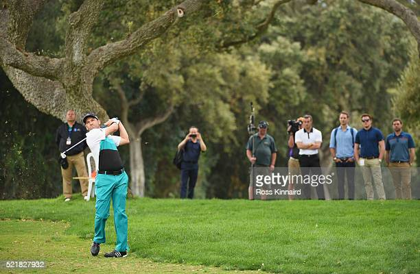 Sergio Garcia of Spain is watched by Real Madrid and Wales footballer Gareth Bale as he plays his second shot on the 18th hole during the final round...