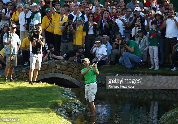 Sergio Garcia of Spain plays into the 17th green whilst standing in the water during the third round of the Andalucia Masters at Valderrama on...