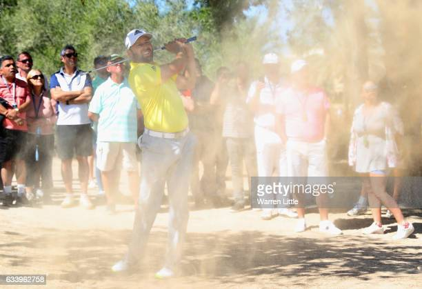 Sergio Garcia of Spain plays out of the sand on the second hole during the final round of the Omega Dubai Desert Classic on the Majlis course at...