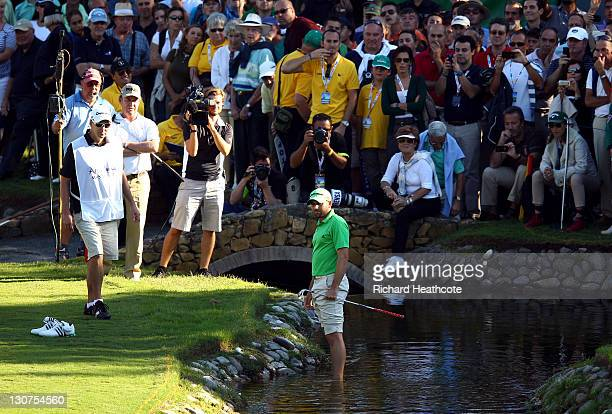 Sergio Garcia of Spain prepares to play into the 17th green whilst standing in the water during the third round of the Andalucia Masters at...