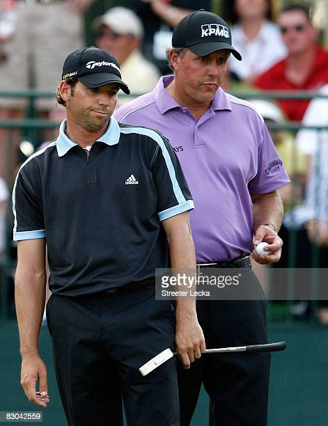 Sergio Garcia of Spain reacts to a putt as Phil Mickelson watches on at the 18th green during the final round of THE TOUR Championship presented by...