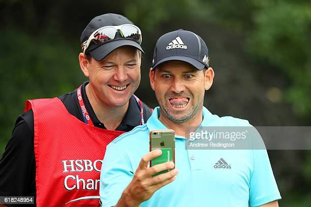 Sergio Garcia of Spain reacts to his phone with caddie Glen Murray during a proam round prior to the start of the WGC HSBC Champions at Sheshan...