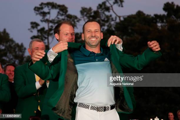 Sergio Garcia of Spain receives the Green Jacket from Masters champion Danny Willett of England after the final round of the Masters at Augusta...