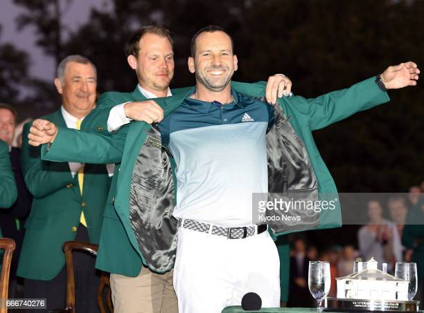 Sergio Garcia of Spain receives the Masters green jacket from 2016 Masters champion Danny Willett of England at Augusta National Golf Club on April 9...