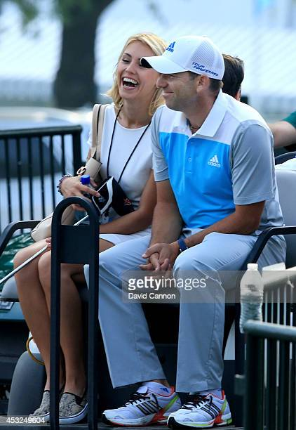 Sergio Garcia of Spain rides with girlfriend Katharina Boehm during a practice round prior to the start of the 96th PGA Championship at Valhalla Golf...