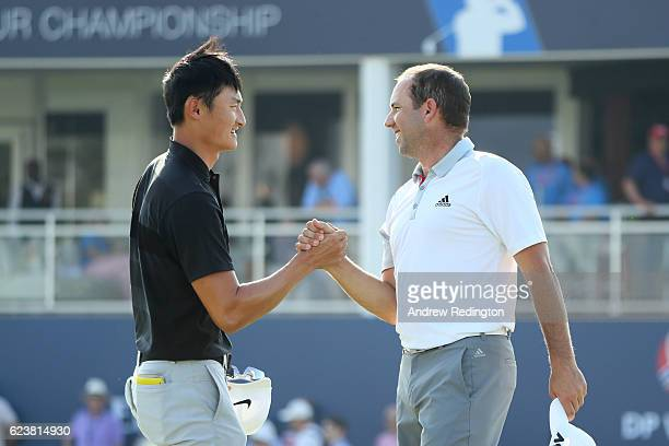 Sergio Garcia of Spain shakes hands with Haotong Li of China on the 18th green during day one of the DP World Tour Championship at Jumeirah Golf...