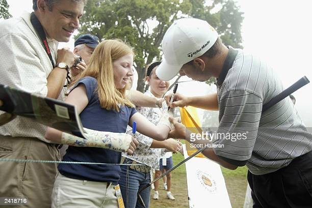 Sergio Garcia of Spain signs the arm casts of golf fan Amanda Klee from Pittsburgh Pennsylvania on the tenth tee during practice for the 85th PGA...