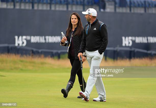Sergio Garcia of Spain walks on the 18th with his girlfriend Angela Akins during previews ahead of the 145th Open Championship at Royal Troon on July...