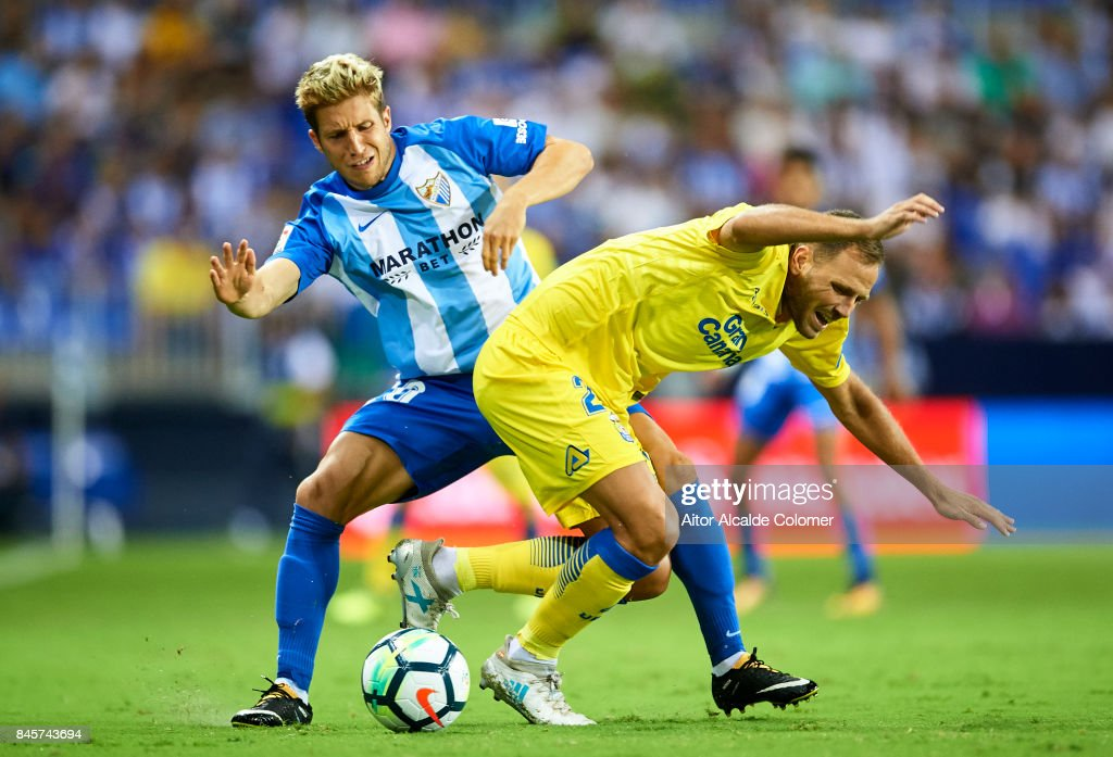Sergio Gontan 'Keko' of Malaga CF (L) competes for the ball with Ximo Navarro of Union Deportiva Las Palmas (R) during the La Liga match between Malaga and Las Palmas at Estadio La Rosaleda on September 11, 2017 in Malaga, .