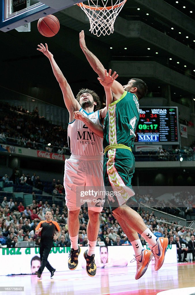 Sergio Llull, #23 of Real Madrid competes with Krunoslav Simon, #4 of Unicaja Malaga during the 2012-2013 Turkish Airlines Euroleague Top 16 Date 11 between Real Madrid v Unicaja Malaga at Palacio Deportes Comunidad de Madrid on March 15, 2013 in Madrid, Spain.