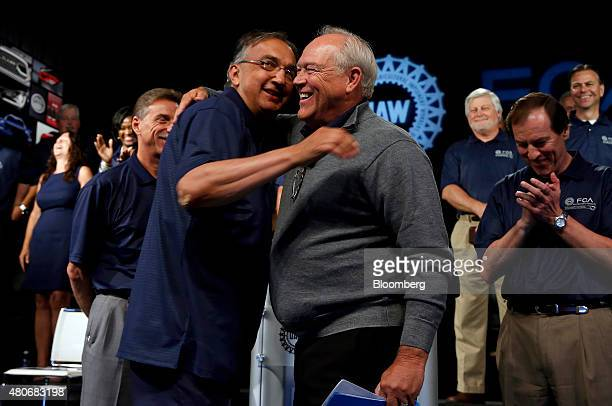 Sergio Marchionne chief executive officer of Fiat Chrysler Automobiles NV left and Dennis Williams president of the United Auto Workers union embrace...