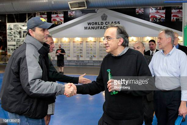 Sergio Marchionne chief executive officer of Fiat SpA and Chrysler Group LLC center shakes hands with a Chrysler Group employee during an event at...