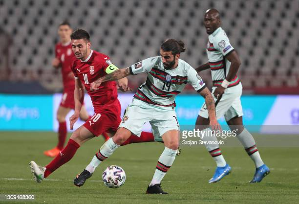 Sergio Oliveira of Portugal and Dusan Tadic of Serbia battle for the ball during the FIFA World Cup 2022 Qatar qualifying match between Serbia and...