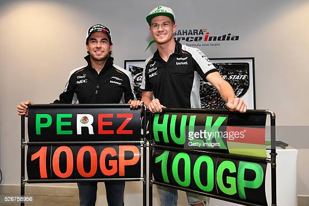 Sergio Perez of Mexico and Force India and Nico Hulkenberg of Germany and Force India celebrate participating in 100 Grand Prix during qualifying for...