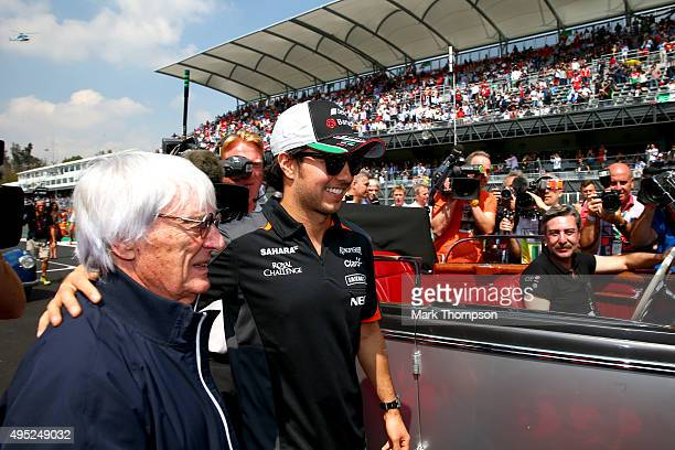 Sergio Perez of Mexico and Force India speaks with F1 supremo Bernie Ecclestone as he takes part in the drivers' parade before the Formula One Grand...