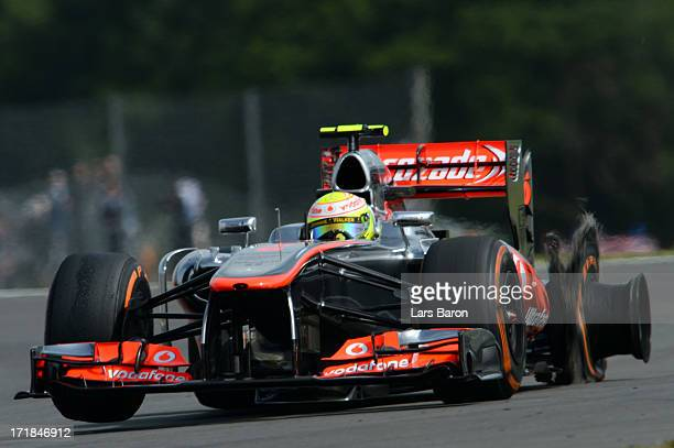 Sergio Perez of Mexico and McLaren drives as his left rear tyre fails during the final practice session prior to qualifying for the British Formula...