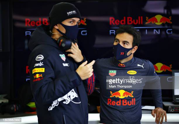 Sergio Perez of Mexico and Red Bull Racing talks with Alexander Albon of Thailand and Red Bull Racing in the garage during the Red Bull Racing...