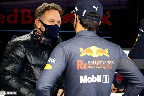 Sergio Perez of Mexico and Red Bull Racing talks with Red Bull Racing Team Principal Christian Horner in the garage during the Red Bull Racing...