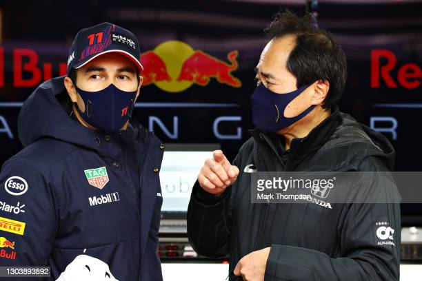 Sergio Perez of Mexico and Red Bull Racing talks with Toyoharu Tanabe of Honda during the Red Bull Racing Filming Day at Silverstone on February 24,...