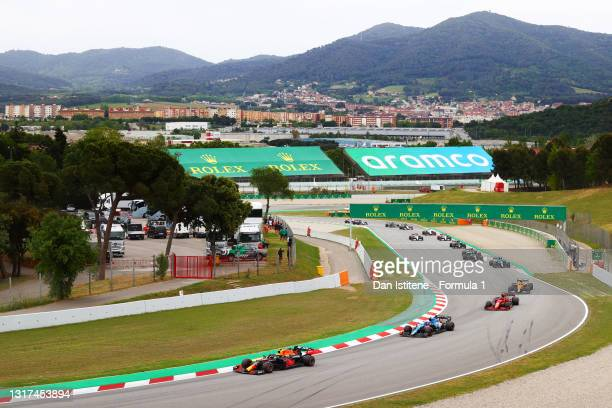 Sergio Perez of Mexico driving the Red Bull Racing RB16B Honda leads Esteban Ocon of France driving the Alpine A521 Renault and Carlos Sainz of Spain...