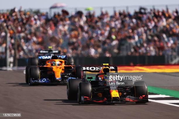 Sergio Perez of Mexico driving the Red Bull Racing RB16B Honda leads Daniel Ricciardo of Australia driving the McLaren F1 Team MCL35M Mercedes during...