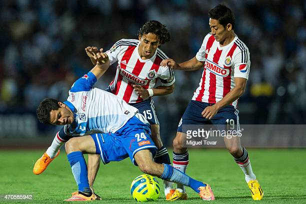 Sergio Perez of Puebla fights for the ball with Fernando Arce and Jose Toledo of Chivas during a Championship match between Puebla and Chivas as part...