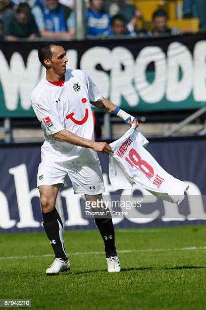 Sergio Pinto of Hannover celebrates with the jersey of Michael Tarnat during the Bundesliga match between Arminia Bielefeld and Hannover 96 at the...