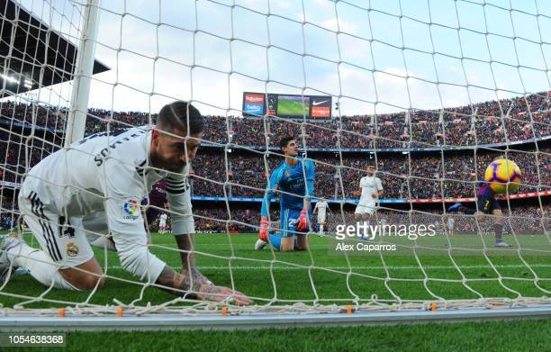 Sergio Ramos and Thibaut Courtois of Real Madrid react as Philippe Coutinho of Barcelona scores his sides first goal during the La Liga match between...