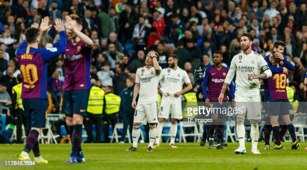 Sergio Ramos of Real Madrid and Luka Modric of Real Madrid looks dejected Lionel Messi and Ivan Rakitic of Barcelona celebrate after winning the La...