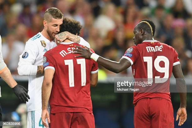 Sergio Ramos of Real Madrid and Sadio Mane of Liverpool console Mohamed Salah of Liverpool as he leaves the pitch injured during the UEFA Champions...