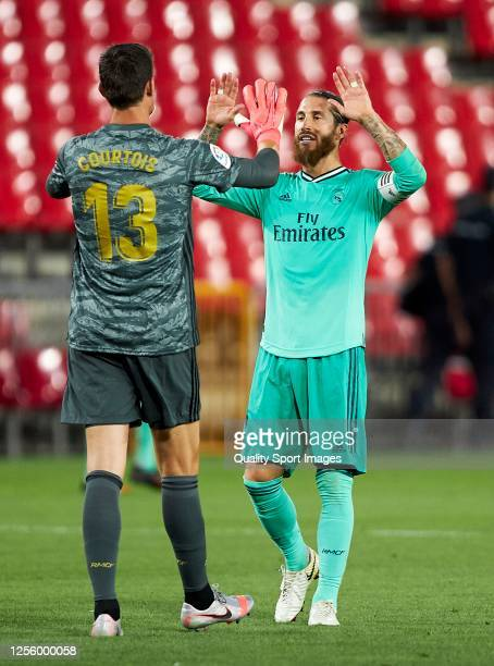 Sergio Ramos of Real Madrid and Thibaut Courtois of Real Madrid celebrate after the Liga match between Granada CF and Real Madrid CF at Nuevo Los...