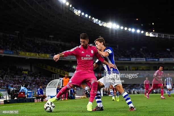 Sergio Ramos of Real Madrid CF competes for the ball with Sergio Canales of Real Sociedad during the La Liga match between Real Sociedad de Futbol...