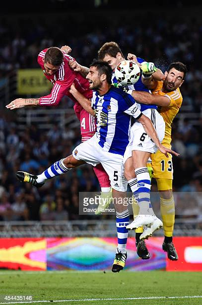 Sergio Ramos of Real Madrid CF heads the ball towards goal under a challenge by Markel Bergara Larranaga Inigo Martinez and Enaut Zubikarai of Real...