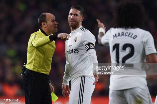 Sergio Ramos of Real Madrid CF is shown a yellow card by the referee Mateu Lahoz during the Copa del Semi Final first leg match between Barcelona and...