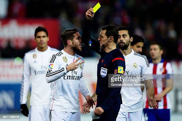 Sergio Ramos of Real Madrid CF protests to the referee Close Gomez as he shows the yellow card after a penalty over Raul Garcia of Atletico de Madrid...
