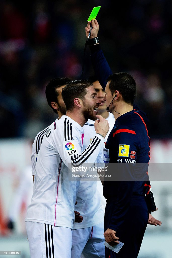 Sergio Ramos (L) of Real Madrid CF protests to the referee Close Gomez (R) as he shows the yellow card after a penalty over Raul Garcia of Atletico de Madrid during the Copa del Rey Round of 16 first leg match between Club Atletico de Madrid and Real Madrid CF at Vicente Calderon Stadium on January 7, 2015 in Madrid, Spain.