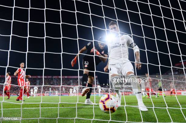 Sergio Ramos of Real Madrid CF takes the ball from the net after scoring his team's first goal from the penalty spot during the La Liga match between...