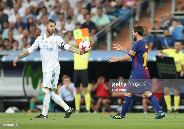 Sergio Ramos of Real Madrid CF throws the ball in the air beside Lionel Messi of FC Barcelona after Barcelona were awarded a free kick during the...