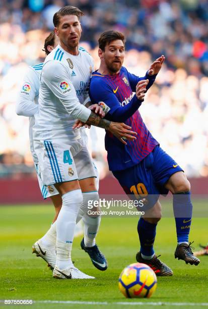 Sergio Ramos of Real Madrid challenges Lionel Messi of Barcelona during the La Liga match between Real Madrid and Barcelona at Estadio Santiago...