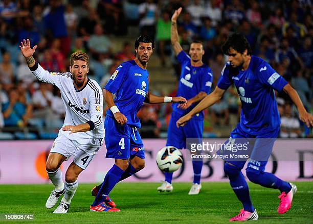 Sergio Ramos of Real Madrid claims for a foul while Miguel Torres and Adrian Colunga of Getafe leads the ball during the la Liga match between Getafe...