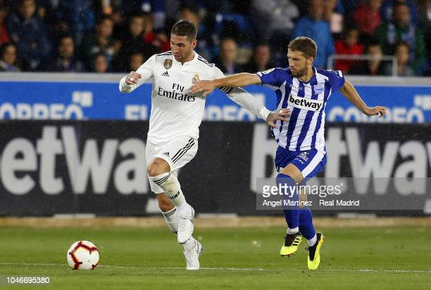 Sergio Ramos of Real Madrid competes for the ball with Darko Brasanac of Deportivo Alaves during the La Liga match between Deportivo Alaves and Real...