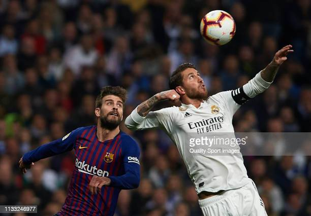 Sergio Ramos of Real Madrid competes for the ball with Gerard Pique of Barcelona during the La Liga match between Real Madrid CF and FC Barcelona at...